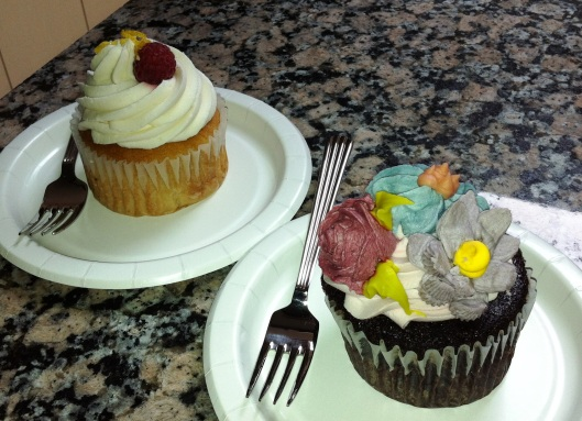 A chocolate cupcake and a vanilla cupcake with a raspberry center!
